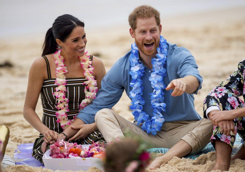 En esta foto del 19 de octubre del 2018, el príncipe Enrique de Inglaterra y su esposa Meghan, duquesa de Sussex, se reúnen con un grupo local de surfistas comocido como OneWave mientras crean conciencia sobre la salud mental y el bienestar de una manera divertida en la playa de Bondi Beach en Sydney, Australia. (Dominic Lipinski/Pool via AP)